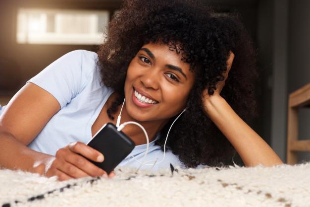 close-up-mulher-negra-em-casa-sorrindo-com-telefone-celular-e-fones-de-ouvido_33839-8812